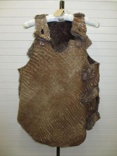Sheepskin waistcoat, Malcolm McLaren and Vivienne Westwood, 1982, Britain. Brown sheepskin thigh-length waistcoat with toggle closures down left side and at both shoulders. Sheepskin.