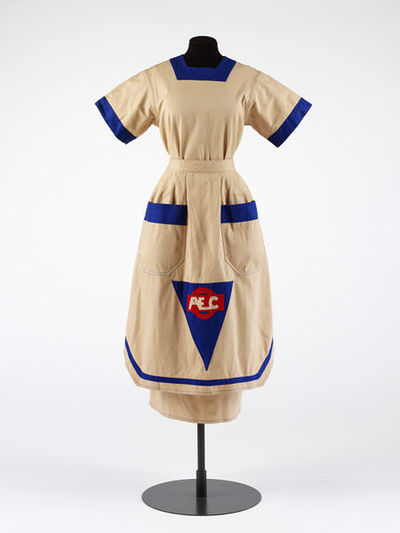 Dress, with apron, beige cotton with blue trim, by William Brown, Great Britain, 1984.Beige cotton twill dress and apron. Beige cotton twill dress, with blue trim on the collar and sleeves, and press stud fastening down...