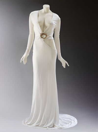 Ensemble, white silk jersey evening dress with a cutaway waist and decorative brooch with gold leather shoes, Tom Ford for Gucci, Autumn/Winter 2004/5, Italy.Leather, white silk viscose jersey, gold paste and diamantés.