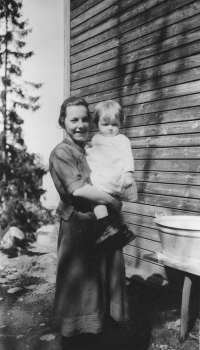 Kvinne med barn på armen ved en vaskebalje