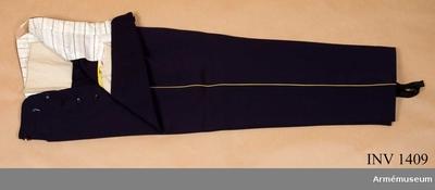 Långbyxor m/1886, Långbyxor m/1886 för officer vid Skaraborgs regemente : Stl 50. Mörkblå kamgarnsdiagonal med gul klädeslist längs yttersömmen. Julpknäppta med fem svarta bakelitknappar, små. I midjan sex knappar för...