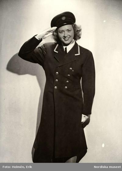 Image from object titled Kvinna i NK-uniform gör honnör. Nordiska Kompaniet i Stockholm.
