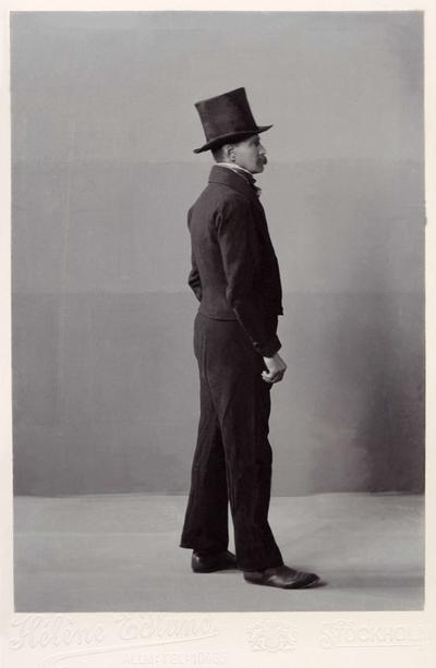Image from object titled Man i folkdräkt med lång byxa, kort jacka och och hög hatt