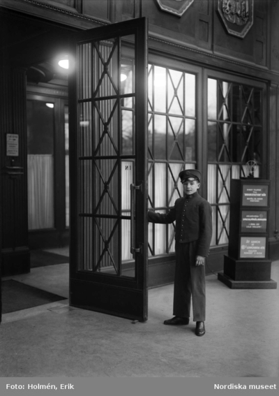 Image from object titled Dörrvakt. Pojke i NK-uniform håller upp dörr.