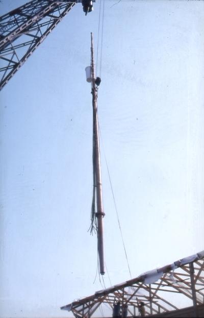 Masten løftes på plass av flytekran fra Oslo havnevesen