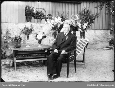 En eldre herre sitter i en stol foran flere blomsteroppsatser