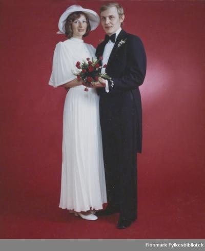 Image from object titled Et brudepar fotografert mot en rød bakgrunn