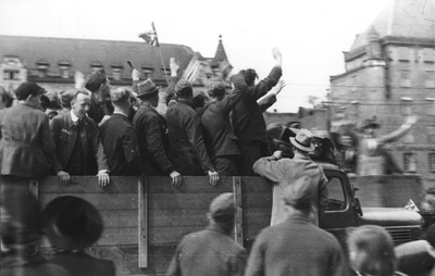 Image from object titled Soldater og sivile på et lasteplan omkranset av tilskuere som hilser og vifter med flagg