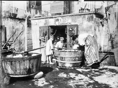 Personer vasker seg fra en tønne med vann