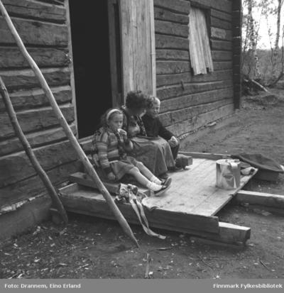 Image from object titled Tre personer sitter på et platting foran en hytte