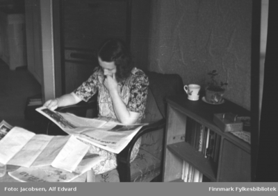 Image from object titled Aase Jacobsen sitter i en lenestol med avisa i fanget