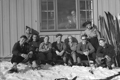 Image from object titled Ukjent gruppe mennesker soler seg i husveggen på skitur