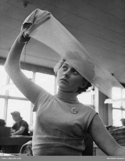 Image from object titled Kontroll av nylonstrumpor vid Malmö Strumpfabrik. En kvinna håller upp en strumpa mot ljuset för att undersöka kvaliteten.