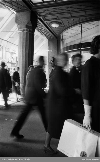 Image from object titled Människor passerar ut och in i NK:s entré. I mitten står dörrvärden.