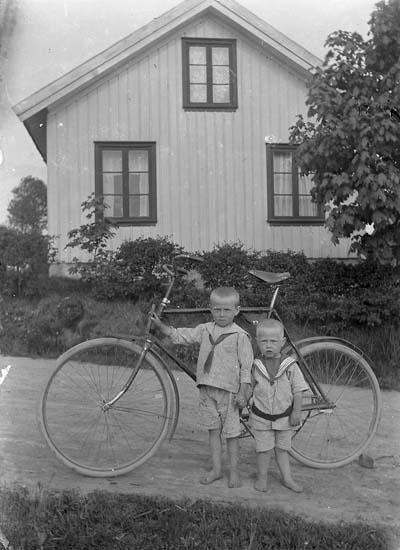 """Image from object titled Enligt notering: """"Ett hus en cykel och två små""""."""