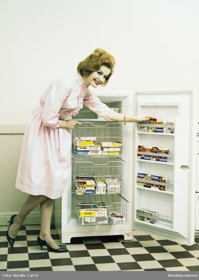 Image from object titled Kvinna i ljusrosa klänning med volang och svarta skor med taxklack visar upp en frys med mat från Findus.