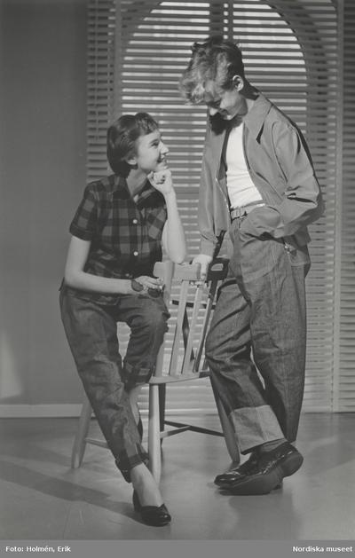 Image from object titled Tonårsmode. Flicka i rutig skjorta och jeans från Melka sitter på en stol. Pojke i poplinjacka, vit t-shirt och jeans står bredvid. Persienn i bakgrunden.
