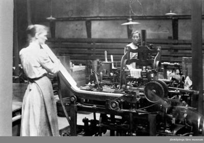 Image from object titled Svenska Tändsticksfabriken i Jönköping. Två kvinnor arbetar vid paketeringsmaskinen.