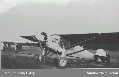 """Image from object titled Text på baksidan: """"Lindbergs flugskep Wi tog detta här kort i sommar. Harry Johnson"""". Charles Lindbergh (1902 - 1974) genomförde 1927 den första ensamflygningen över Atlanten med sitt plan """"Spirit of St. Louis""""."""