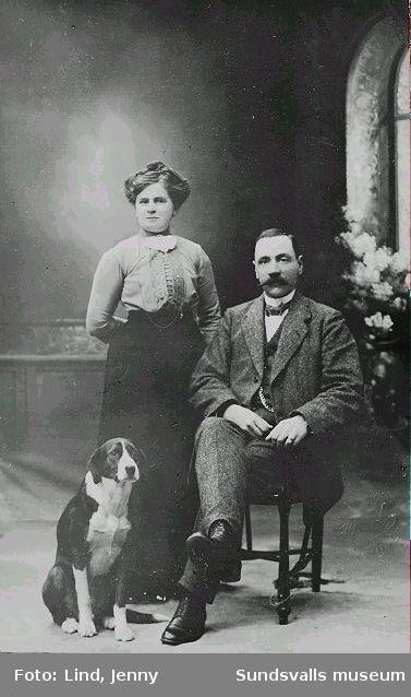 ateljéporträtt av medelålders par med hund