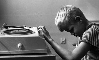 Image from object titled Blind pojke, 11 juni 1966  En blind pojke i tioårsåldern klädd i randig T-shirt spelar en skiva som ligger på en skivspelare.