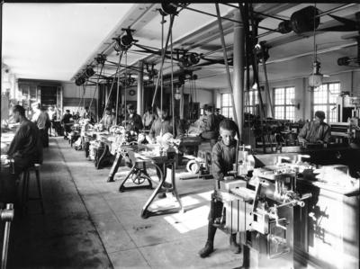 Image from object titled Interiör från Gustaf LM Ericssons Automobilfabrik. Arbetare vid maskinerna i verkstaden på Liljeholmen. Pojken i förgrunden lär upp sig på kipphyvel, en lämplig nybörjarmaskin.