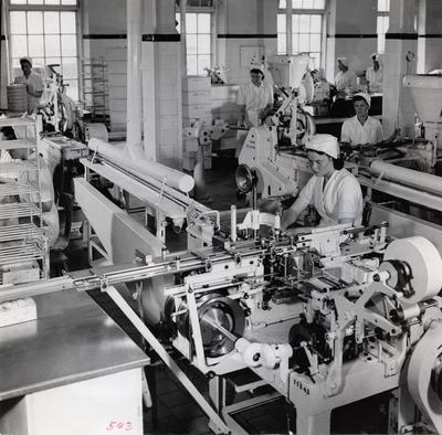 Image from object titled AB Cloetta, Ljungsbro, interiör. Inpackningsmaskiner för kola. Kolabitarna skäras till, slås in i vaxpapper och erhålla slutligen ett omslag i form av en tryckt pappersbanderoll - allt i samma anläggning.