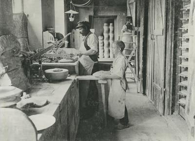 Image from object titled Tallriksformare Gottfried Enberg med springpojkar i ett av verkstadshusen. Formningen sker med hjälp av en stegmaskin. Personer: Gottfried Enberg.