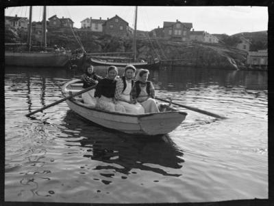Fyra kvinnor i en roddbåt. Ankrade fiskebåtar i bakgrunden. Troligen Fiskebäckskil, Bohuslän.