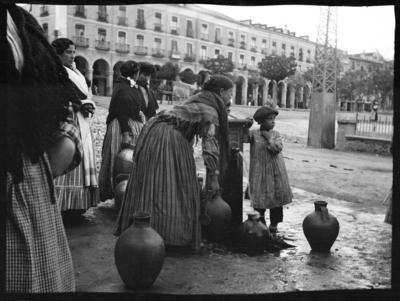 Spanien. Kvinnor och barn vid en vattenpump intill ett torg. Krukor fylls med vatten.