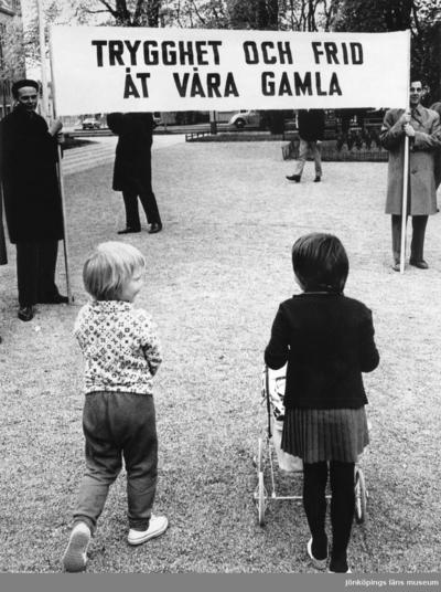 Image from object titled En demonstration med text på banderollen: Trygghet och frid åt våra gamla. Två barn i förgrunden, den ena kör en dockvagn.