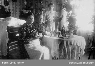 Kvinnor dricker kaffe, kanske namnsdagskaffe. Bilden i form av privattaget vykort som adresserats till (farmor) Fru Josefina Andersson, Sundsvall. daterat 21/8 1916 med text Hjärtlig gratulation på Josefinadagen av Fru...