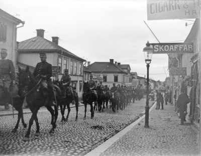 Militärtrupp på häst uppför Kungsgatan, Enköping, sett från Kungsgatan 16 mot söder
