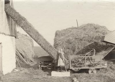 Image from object titled Halmpress kombinerad med tröskverk från Bröderna Anderssons Gjuteri, Skåne. Denna press såld 1910, var ännu i användning 1926. Flickan slår knuten på halmbalarna.