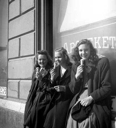 Image from object titled En trio unga damer med glass i vårsolen utanför apoteket Örnen på Kungsgatan 14 1945.