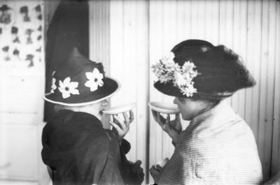 """Image from object titled Två okända kvinnor """"sörplar"""" kaffe från kaffefat. Foto i maj 1919."""