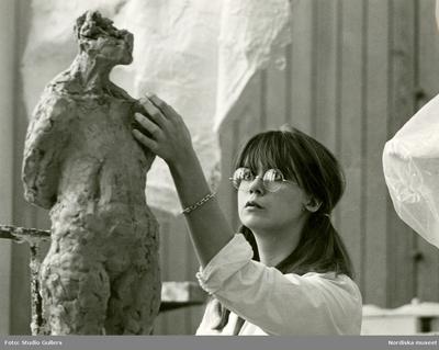 Image from object titled En elev vid Konstfackskolan modellerar en skulptur i lera.