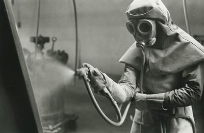 Image from object titled Interiör. Badkarsfabriken. Arbetare iförd skyddsmask med friskluftintag som användes vid manuell emaljsprutning. Personer: okänd