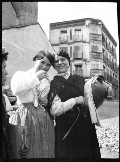 Två leende kvinnor, den ena hållande en kruka. Till vänster skymtar en pojke. Hus i bakgrunden. Troligen Ronda, Spanien.