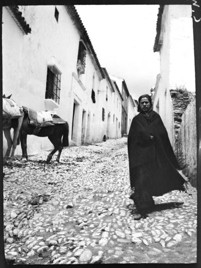 Kvinna på kullerstenslagd gata. Två åsnor i bakgrunden. Troligen Ronda, Spanien.