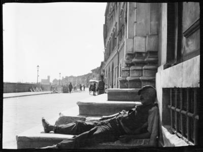 Sovande man lutad mot en husvägg. Troligen Triana eller Sevilla, Spanien