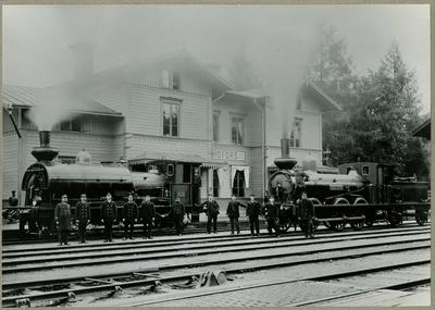 """Hofors station. På spåret syns Gävle-Dala Järnvägs ånglok, GDJ B 10 """"Thore Petré"""" och GDJ C 24, """"Sölve"""".  Personal, från vänster: Stins Lagerström C R, född 1832, avliden 1901. Söderlund, stationsmästare i Valbo 1913...."""