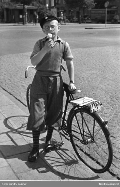 Image from object titled En pojke i golfbyxor, pullover och skärmmössa äter glass vid en cykel