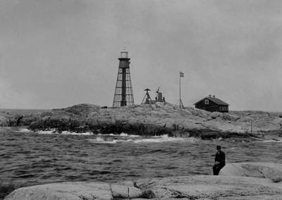 Image from object titled Pater Nosters fyr från syd. I förgrunden sitter en man på en klippa.