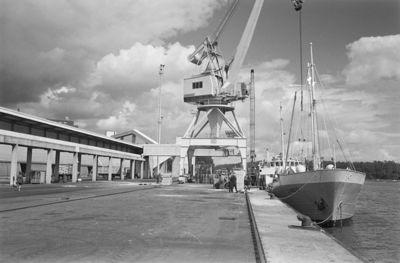 Kuva ottetu satamassa laiturin suuntaisesti. Laiturissa Lindö-niminen laiva. Nostureita, trukkeja ja laatikoita laiturilla.