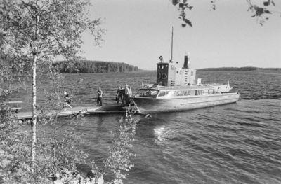 Kuvattu rannalta järvelle päin. Laiturissa katettu moottorivene ja osittain näkyvä höyrylaiva. Matkustajat kävelevät laiturilla rantaa kohti.