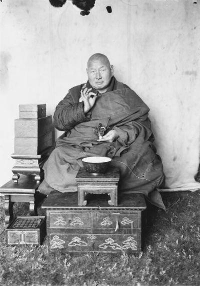 """buddhalainen piispa Toin-Daa-Khambo pitelee """"piispan kukkaa"""" kädessään siunausasennossa"""