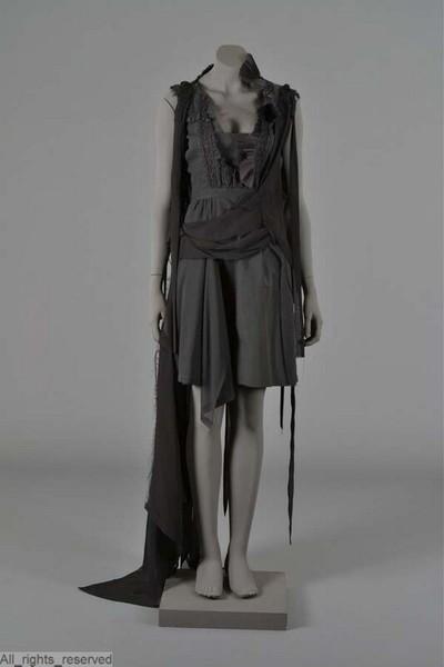 Japon in zwart katoen, mouwloos model met op het corsage uitgeknipte stroken plissé en zwarte machinale kant; over schouder en rok een drapering in zwart voile