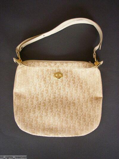 Handtas,  in schildvorm in een beige jacquardweefsel met ingeweven letters Dior; rap. : 8,5 x 11; hengsel in beige leder aan twee rechthoekige metalen beugels; sluit met een ritssluiting; voering in beige leder