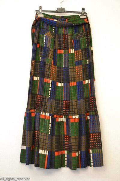 Bruine rok, bedrukt met ruiten in groen, rood, zwart, helblauw en wit; gedeeltelijk geplisseerd; opgezette zak en tailleband met ceintuur in dezelfde stof; ritssluiting